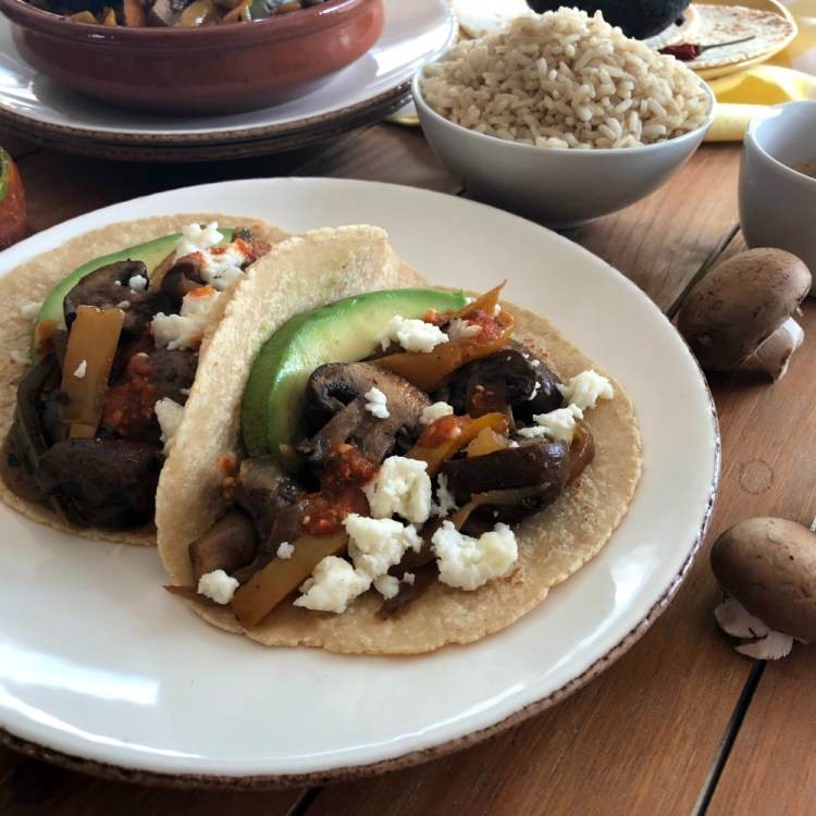 Garnishing the tacos with avocado, red salsa and queso fresco