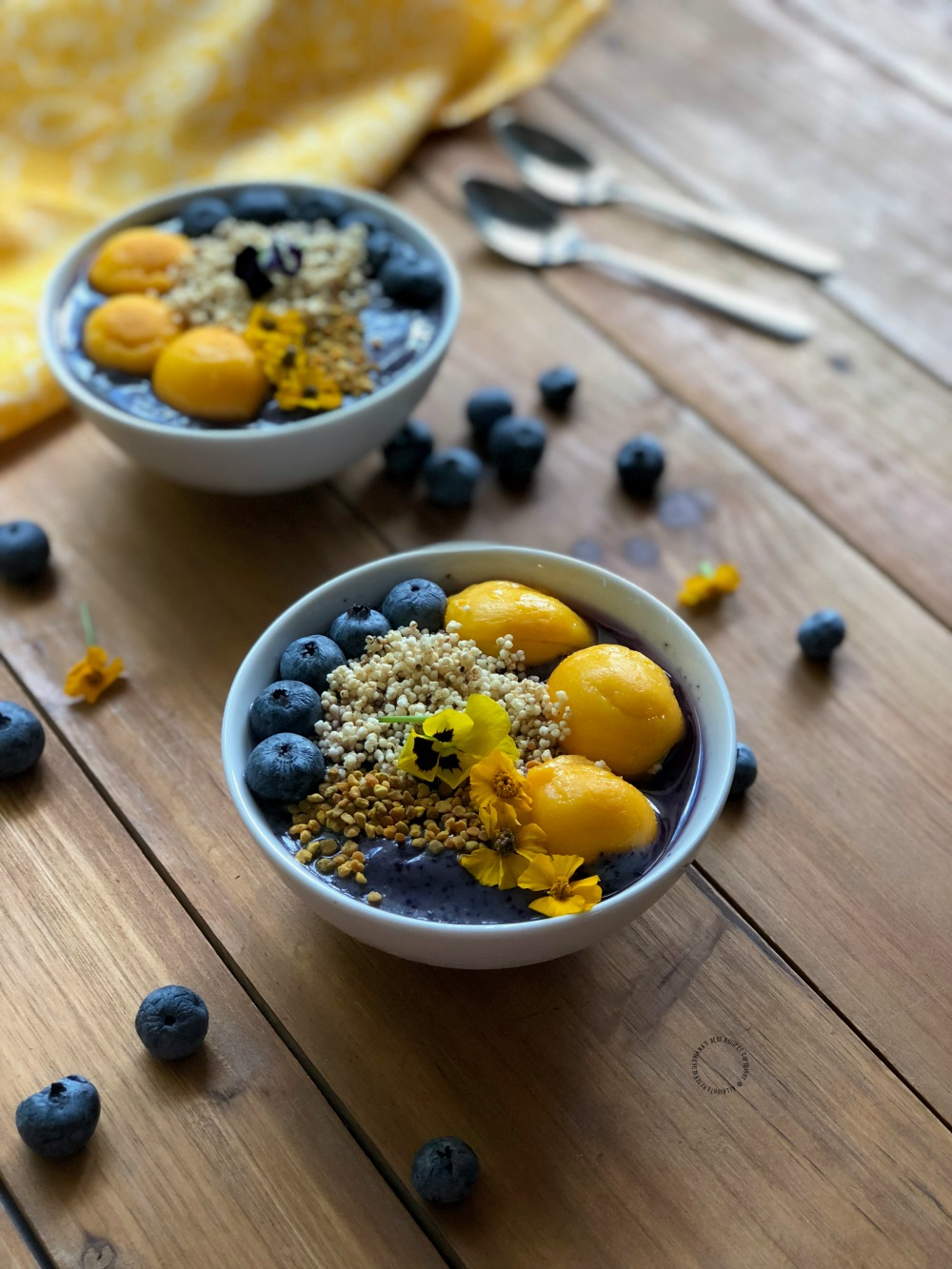Sensible blueberry power smoothie bowl garnished with edible flowers, amaranth and bee pollen