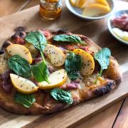 Esta pizza de jamon serrano esta hecha con pan naan, queso manchego, manzana, y espinaca