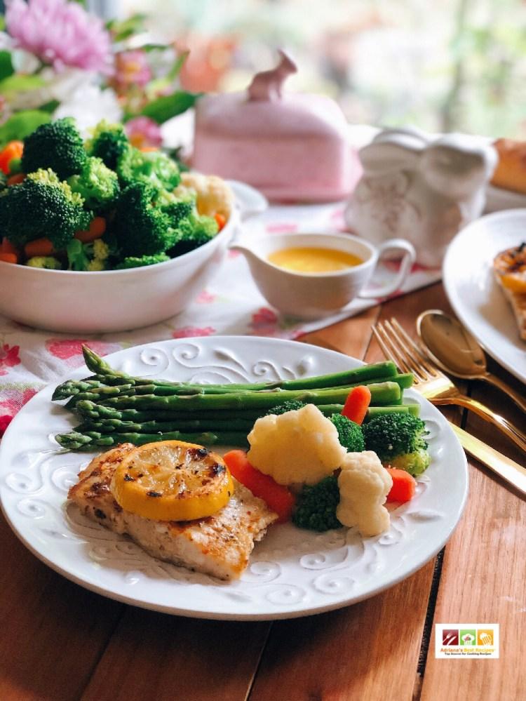 Este platillo con pescado asado es elegante perfecto para la primavera o la pascua. Se sirve en platos blancos con cubiertos dorados.