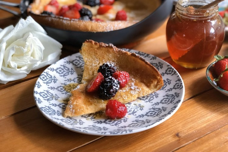 Dutch baby pancakes garnished with berries, honey, and confectioners sugar.