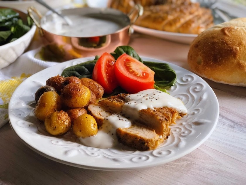 Peppered Turkey Tenderloin with gravy, roasted potatoes, and a spinach tomato salad