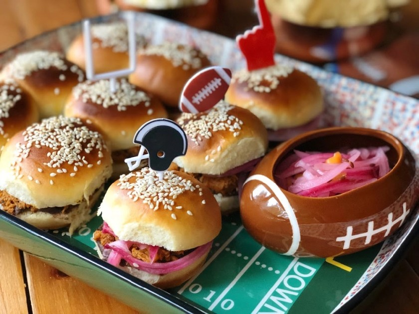 This are the BBQ Pork Pibil Sliders with Refried Beans served on a football themed tray with decorative pins