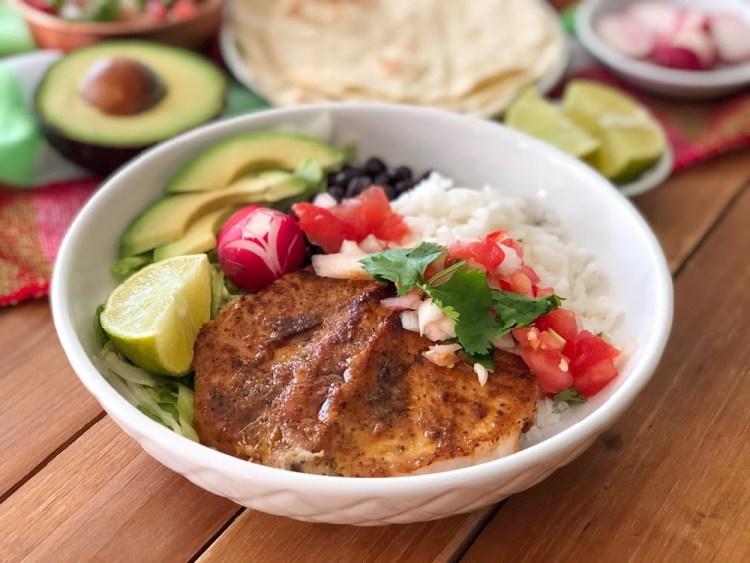 The Chipotle Pork Chops Bowl has grilled boneless pork chops, white rice, black beans, lettuce, avocado slices, radishes, and pico de gallo.