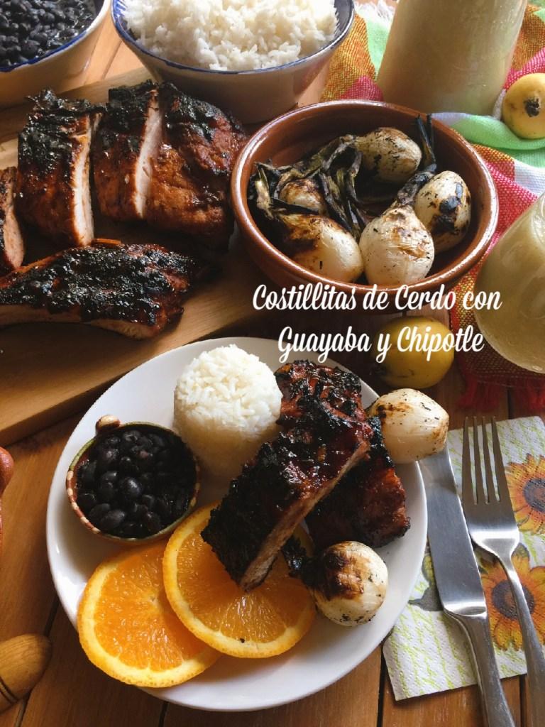 Cena completa de costillas de cerdo al BBQ con cebollitas y rodajas de naranja