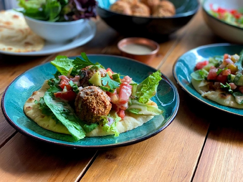 a plate with plant-based meatballs over a bed of greens