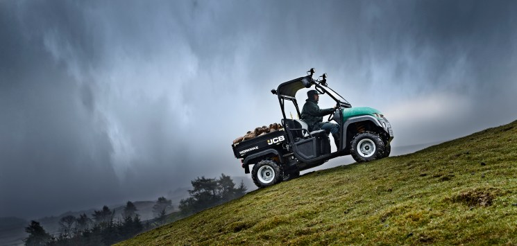 Green and black JCB workman ascending a steep hill with it's cargo of potatoes, set against a stormy sky and misty rain.