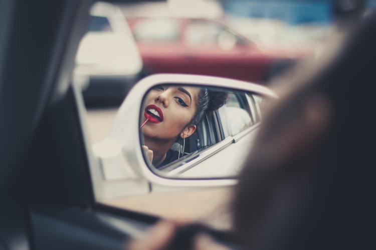 Woman putting on lipstick in the side mirror of her car.