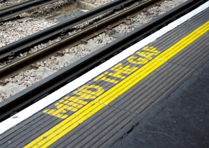 "Painted sign: ""Mind the Gap"" at a railway station"