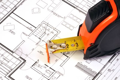 A tape measure and architectural house plan