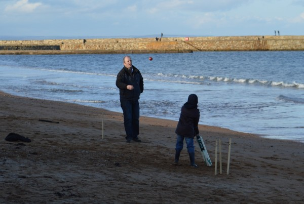Father and son playing cricket on East Sands