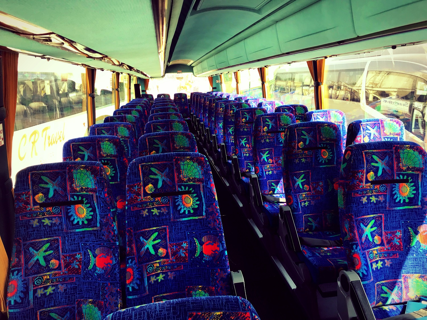 A view of the inside of Advanced Travel's 49 seater Scania Irizar coach, which is available for coach hire in Doncaster. The seats are placed in two rows of double seats, with an aisle down the middle. The back row has five seats next to each other.