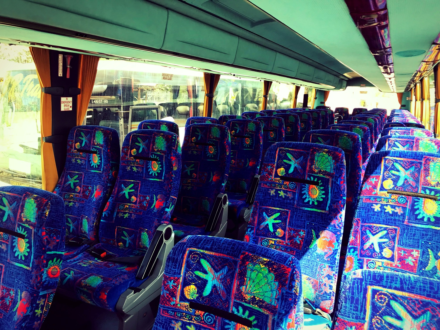 A view of the seats in Advanced Travel's 49 seater Scania Irizar coach, which is available for coach hire in Doncaster. The seats are reclinable and have lap belts. They are covered in a blue fabric with a seashell pattern. There are two rows of double seats with an aisle down the middle. There are two rows of overhead storage compartments above each row of seats.