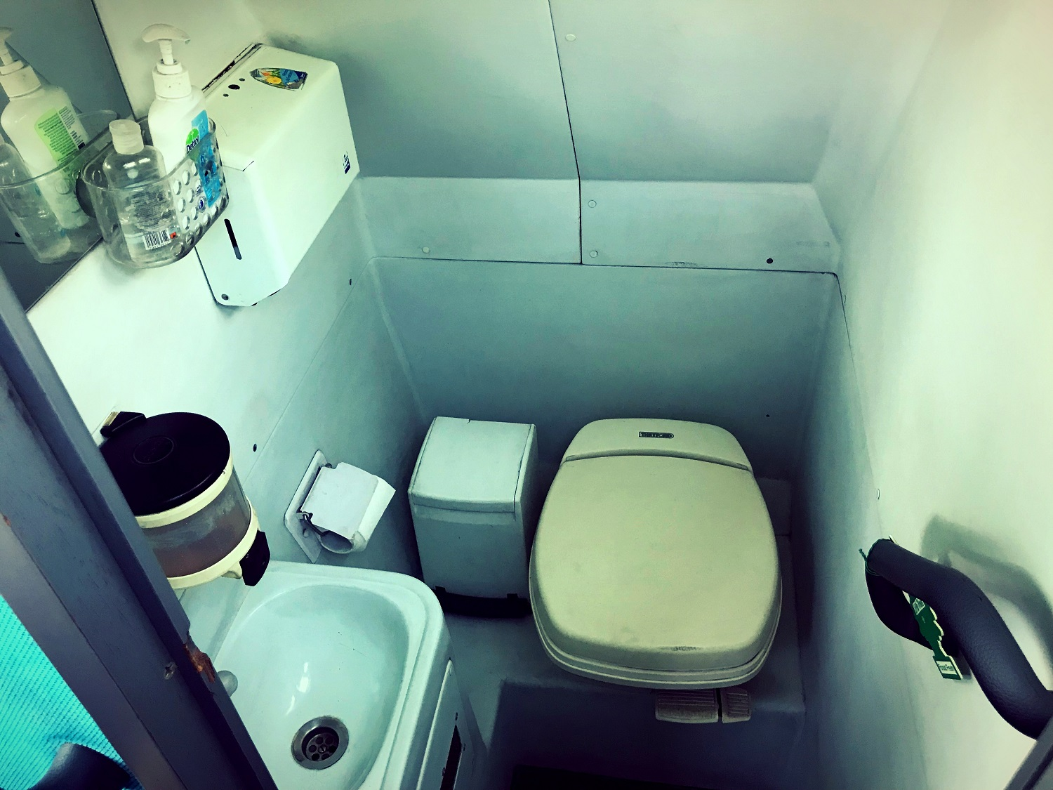 A view of the toilet in Advanced Travel's 49 seater Scania Irizar coach, which is available for coach hire in Rotherham. There is a small cubicle with a hand rail leading into it. There is a toilet, toilet roll dispenser, sink, soap dispenser and hand towel dispenser. There is also a waste paper bin and some additional soaps and cleaning products. There is a small mirror above the sink.