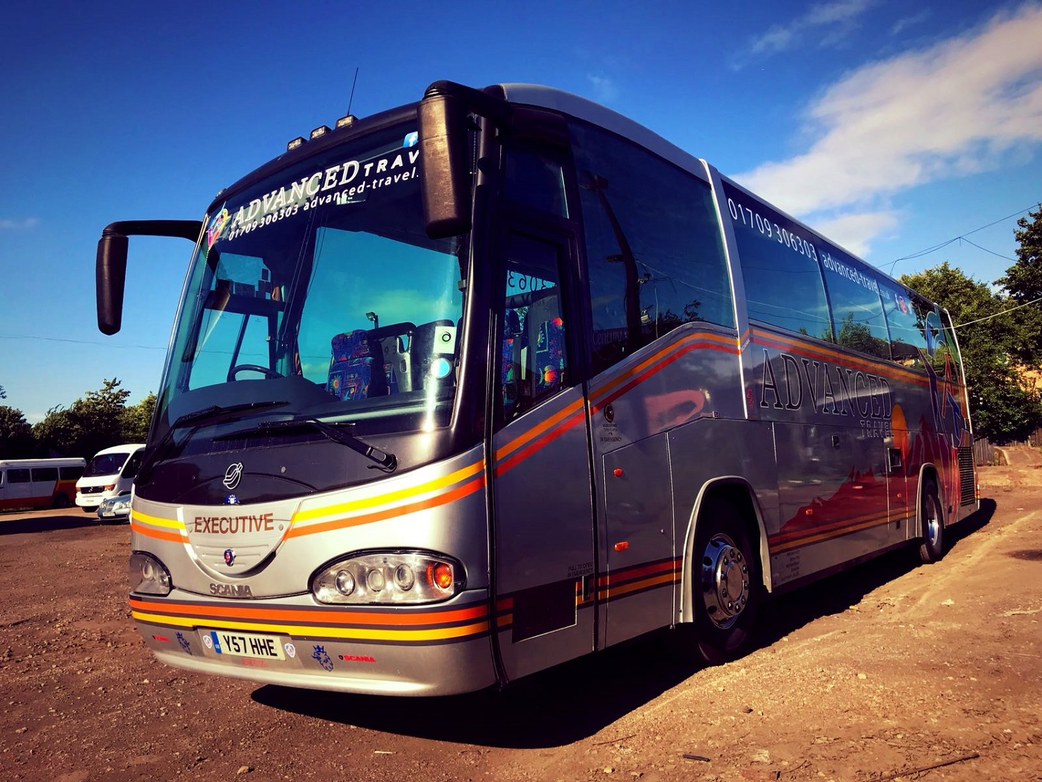 A view of the outside of Advanced Travel's 49 seater Scania Irizar coach, which is available for coach hire in Sheffield. The front and left hand side of the coach are visible. The coach is silver with an orange and yellow border. Advanced Travel's name, logo, website and phone number are displayed at the top of the windscreen and also on the side of the coach.