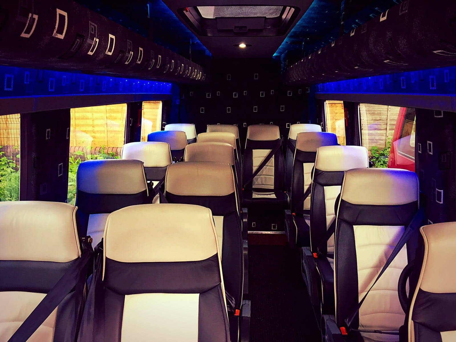 The interior of our Luxury Mercedes Sprinter 16 Seater Minibus. With reclining leather seats with arm-rests and overhead storage.