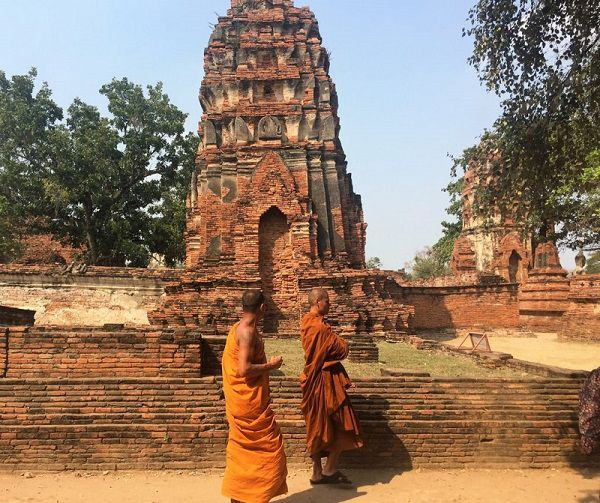Monks walking past a prang in Ayutthaya