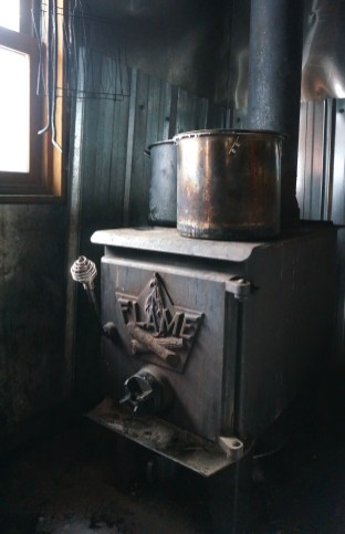 The wood burning stove with pots of melting snow.