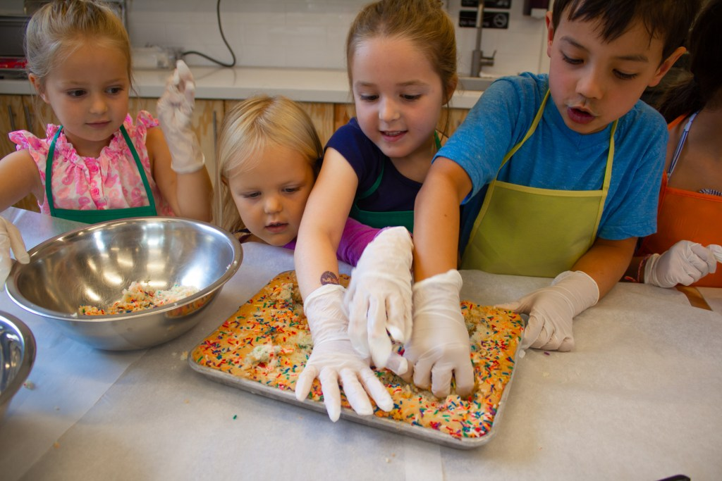 kids crumbling cake for cake truffles in cooking class