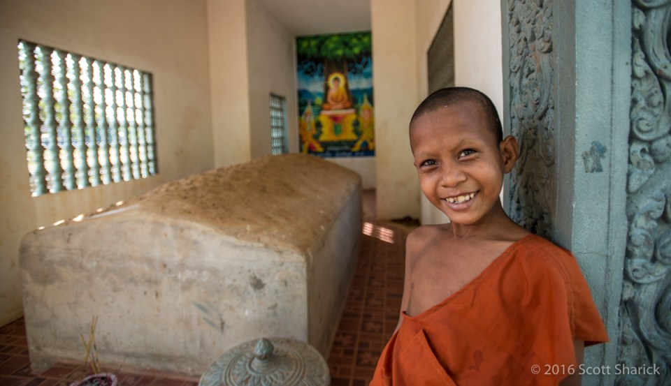 A young monk smiles at the grave of Ta Mok, Brother Number Five.