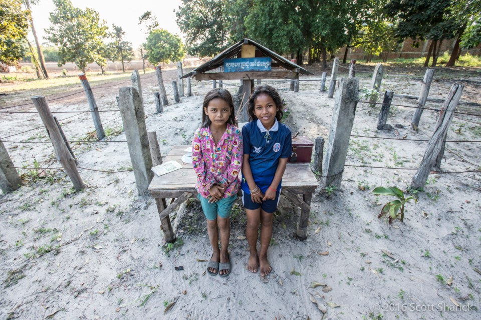 Two local girls pose at the final resting spot of Pol Pot - leader of the Khmer Rouge.