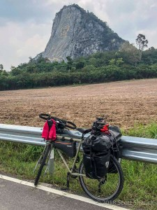 Bicycle rests on a guardrail with the Khao Chi Chan Buddha in the background in Thailand