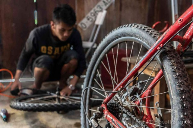 A bicycle mechanic works on a tire in Luang Prabang, Laos