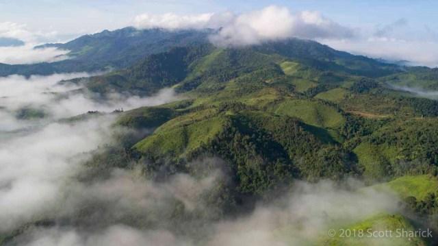 A drones eye view of the mountains in northern Laos with clouds blanketing the valleys.