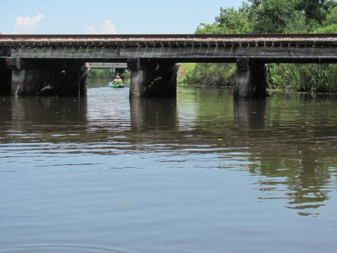 kayak under a bridge on the bayou st john. A fun outdoor date idea that allows you to explore the sites of new orleans and get a lesson in their history.