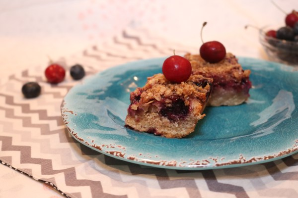 mixed berry crumble bars with few berries in background, making it a perfect summertime dessert.