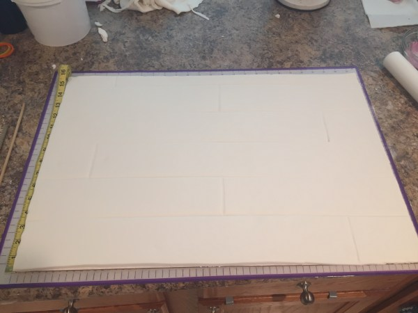 white fondant covering a board. Making lines to look like food for the cake board