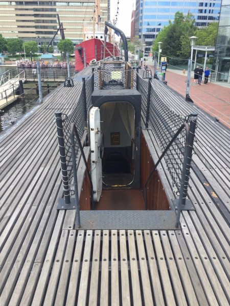 on top the USS Torsk submarine with stairs leading down, You can see the Chesapeakee lightship behind it in Baltimore Maryland.