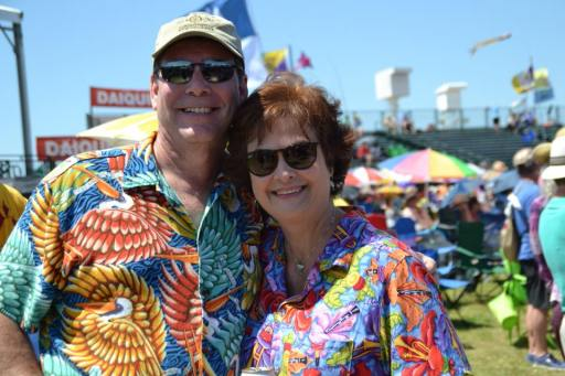 Couple enjoying Jimmy Buffet at New Orleans Jazz Fest. Learn all about New Orleans Jazz and Heritage Festival at adventuresofb2.com