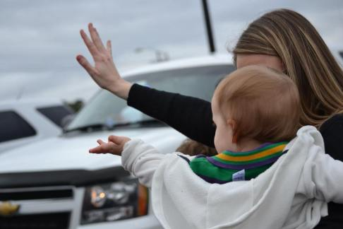 Mom and daughter wave at the parade as it passes by in the streets of new orleans. Learn how to make your Mardi gras trip successful with kids at adventuresofb2.com