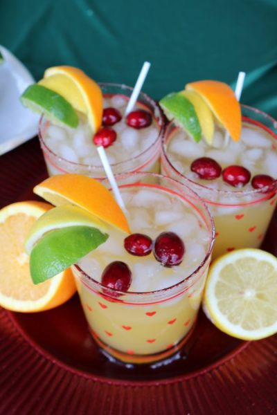 A brightly colored glass of Christmas cheer! Jingle juice is a light fruity cocktail perfect for celebrating at holiday parties! With flavors of pineapple, lemon, lime, apple and orange, perfect for attacking your tastebuds with a delightful Christmas drink!