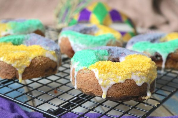 King cake donuts are all the deliciousness of a king cake in a breakfast or dessert doughnut! Cinnamon flavored donut with an extra cinnamon swirl topped with a sweet icing and colored sugar. A fantastic treat for the mardi gras season- Adventures of b2 #glutenfree