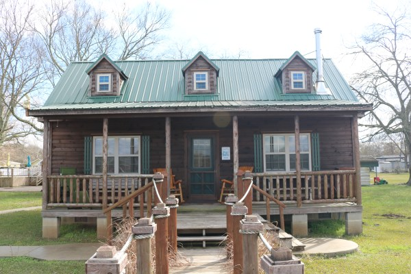 A fantastic view of Cajun Acres Log Cabin in Arnaudville, LA. A cozy quaint cabin available on Airbnb to escape the hustle and bustle of city life. See my experience of this airbnb cabin at adventuresofb2.com