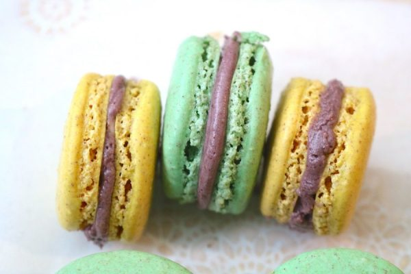 Mardi Gras King Cake Macarons are delightful little macaron with swirls of cinnamon. A light flavor of a king cake just in time for the Mardi Gras season. The fabulous colors of purple, green, and gold make up these delicious macarons. They are perfect for any party to munch on at a parade. - Adventuresofb2.com