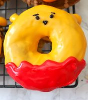 Last step for the Winnie the Pooh donuts is making the face. Make two small black dots for the eyes and a small black dot for the nose. Use a toothpick to bring the nose down into a triangle. Last add small black lines for eyebrows. - adventuresofb2.com