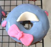 Now you will add accessories for the eeyore donut. Make two small tic tac sized shapes for the ears and a bone shape for the bow. Pinch the middle of the bone and add a small pink dot on top. Last roll out light yellow fondant and cut out a semi-circle or moustache shape for the nose. - Adventuresofb2