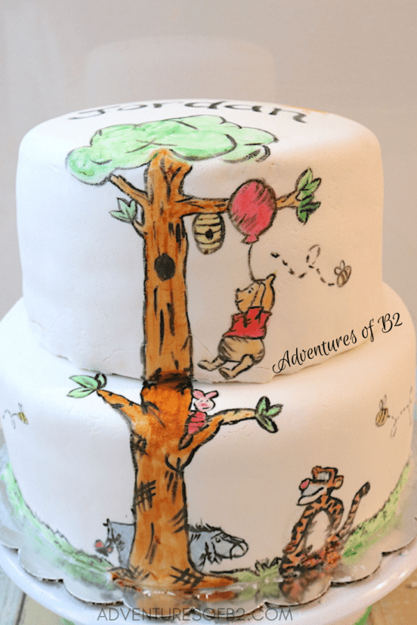 winnie the pooh cake- a two tier cake covered in white fondant and hand painted Winnie the Pooh, Tigger, Eeyore, and piglet. An adorable cake that combines baking with art. - adventuresofb2.com