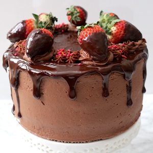 one of the best combinations are chocolate and strawberry! A family favorite and the perfect dessert for any party but especially romantic ones like valentine's day or anniveraries. This showstopping cake is made up of rich chocolate cake layers with chocolate ganache and strawberry filling in between, surrounded by a creamy chocolate buttercream, dripping with chocolate ganache and topped with chocolate covered strawberries. It will definitely make a statement at your next party. - adventuresofb2.com