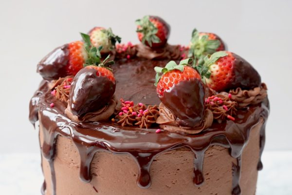 Celebrate Valentine's day with your partner with this romantic cake! Rich chooclate cake with layers of ganache and fresh strawberry filling, wrapped in a creamy chocolate frosting, dripping with chocolate ganache and chocolate covered strawberries. It's over the top for any special occasion. - Adventuresofb2.com