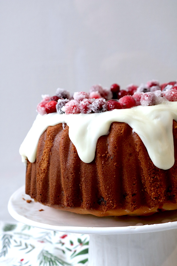 A festive holiday cake. This White Chocolate Cranberry Bundt Cake is a simple cake with filled with cranberries for a hint of sweet and tart. Topped with white chocolate ganache and decorated with sugared cranberries. A delicious Christmas cake for any holiday party. - Adventuresofb2 #whitechocolate #cranberry #holidays #dessert #bundtcake #christmas