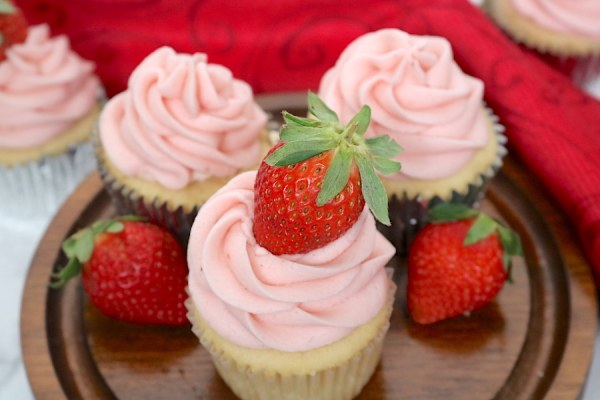 Celebrate Valentine's day with your partner or friends with these delicious cupcakes! It starts with a simple yet tasty vanilla cupcake filled with a whip cream and strawberries topped with a sweet strawberry buttercream. - Adventuresofb2.com
