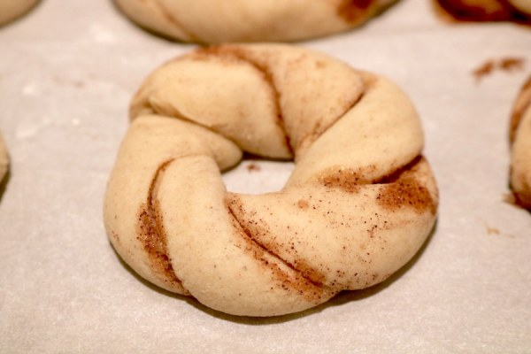 Twist the braid of king cake cookie dough together to form a circle. Place onto parchment paper and bake!