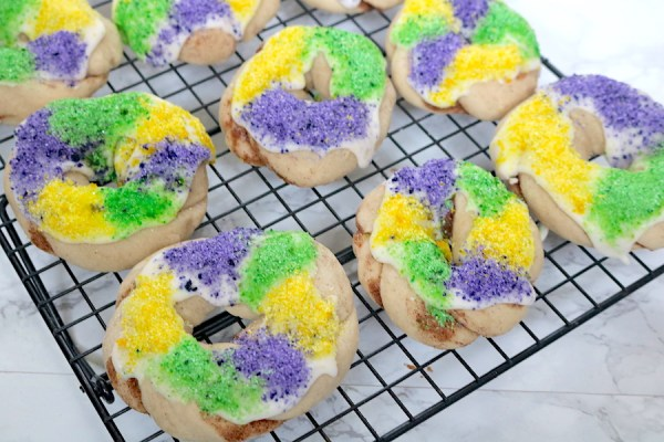 A unique twist on the traditional king cake! It's a mini king cake in cookie form topped with icing and the traditional purple, green and gold sprinkles. It's just what you need for any Mardi Gras party!