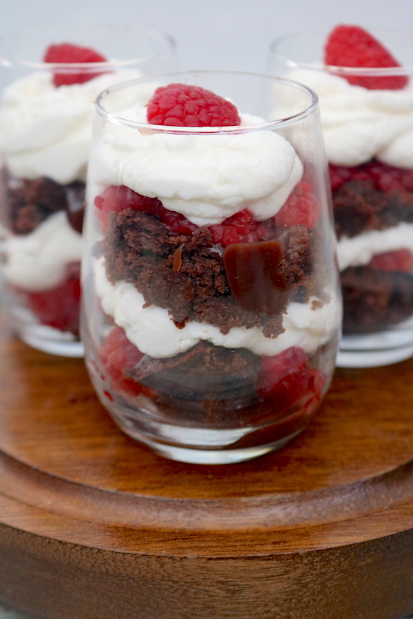 Chocolate raspberry trifles are perfectly portioned mini desserts that will be a hit at your next party! Layers of fudge brownie bites with chocolate raspberry ganache and fresh raspberries with whipped cream layered in between. Perfect for Valentine's day or any day! - adventuresofb2.com #minitrifles #chocolateraspberry #brownies #layereddessert #minidessert