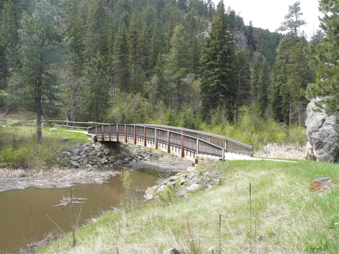 This footbridge at the W end of the campground at Horse Thief Lake leads to the trailhead for the Horsethief Trail No. 14 into the Black Elk Wilderness.