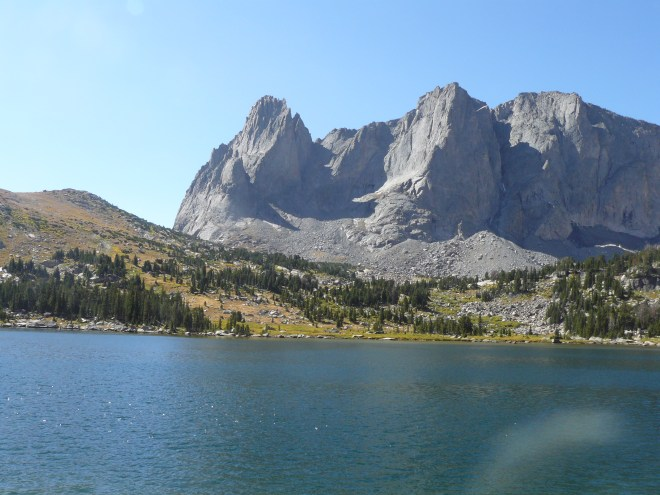 Jackass Pass (ridge on L), War Bonnet Peak (Center L), and Warrior Peaks (R) from Lonesome Lake. Photo looks S.